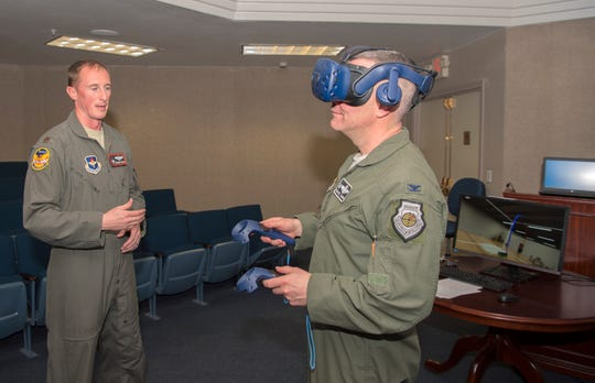 Maj. Christopher Brown, 54th Training Squadron director of staff, shows Col. Joseph Campo, 49th Wing commander, how to use a virtual reality headset, Feb. 20, on Holloman Air Force Base. The virtual reality headsets are intended to improve training for pilots here, by giving them a more realistic, three-dimensional view of the cockpit without being in an aircraft. The presentation was part of the 49th Wing Innovation Shark Tank which Holloman Airmen could present innovative ideas to improve processes, tools and procedures on base.