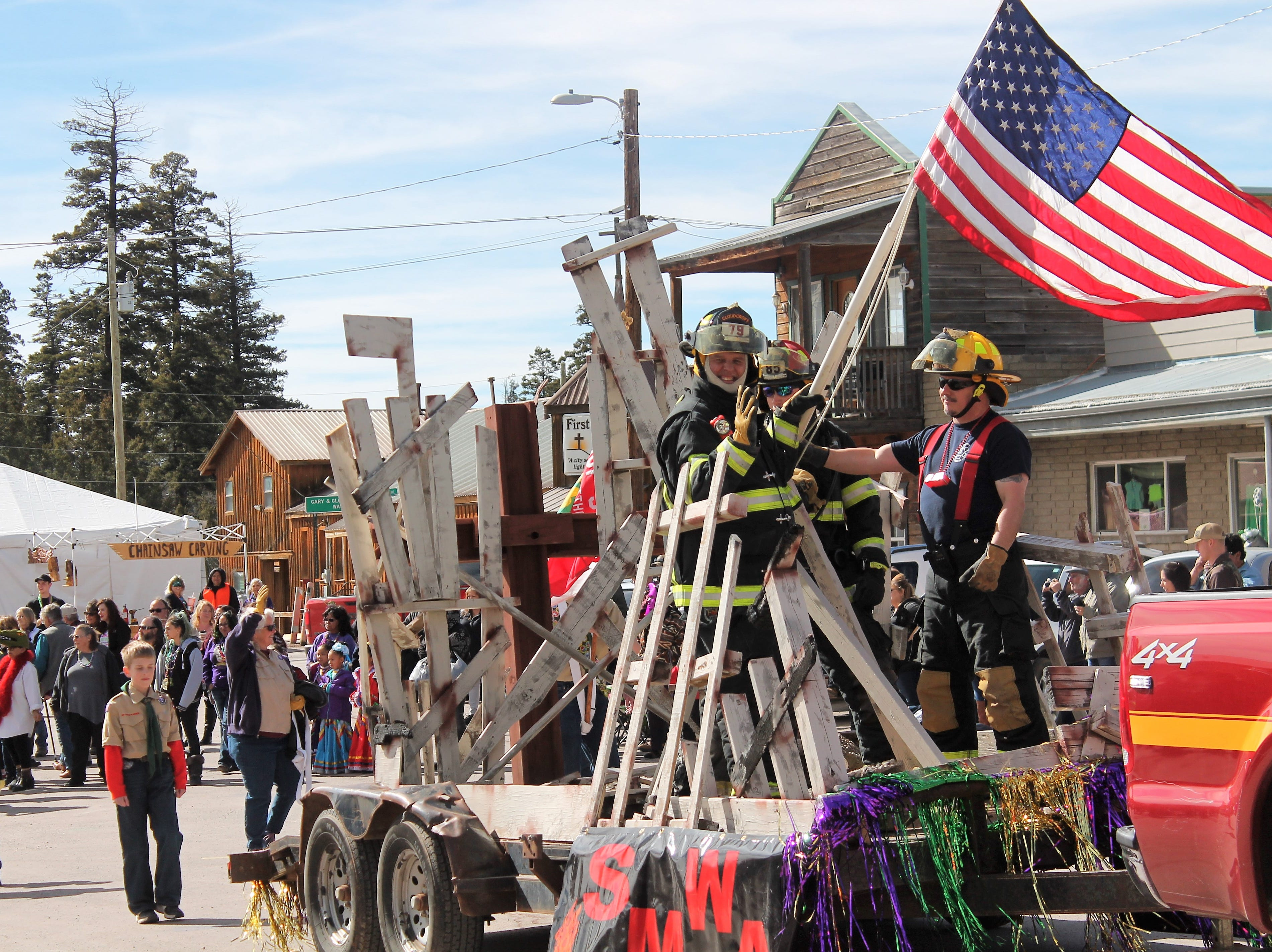 Members of the Cloudcroft Fire Department on their float at the Mardi Gras Parade in Cloudcroft Saturday.