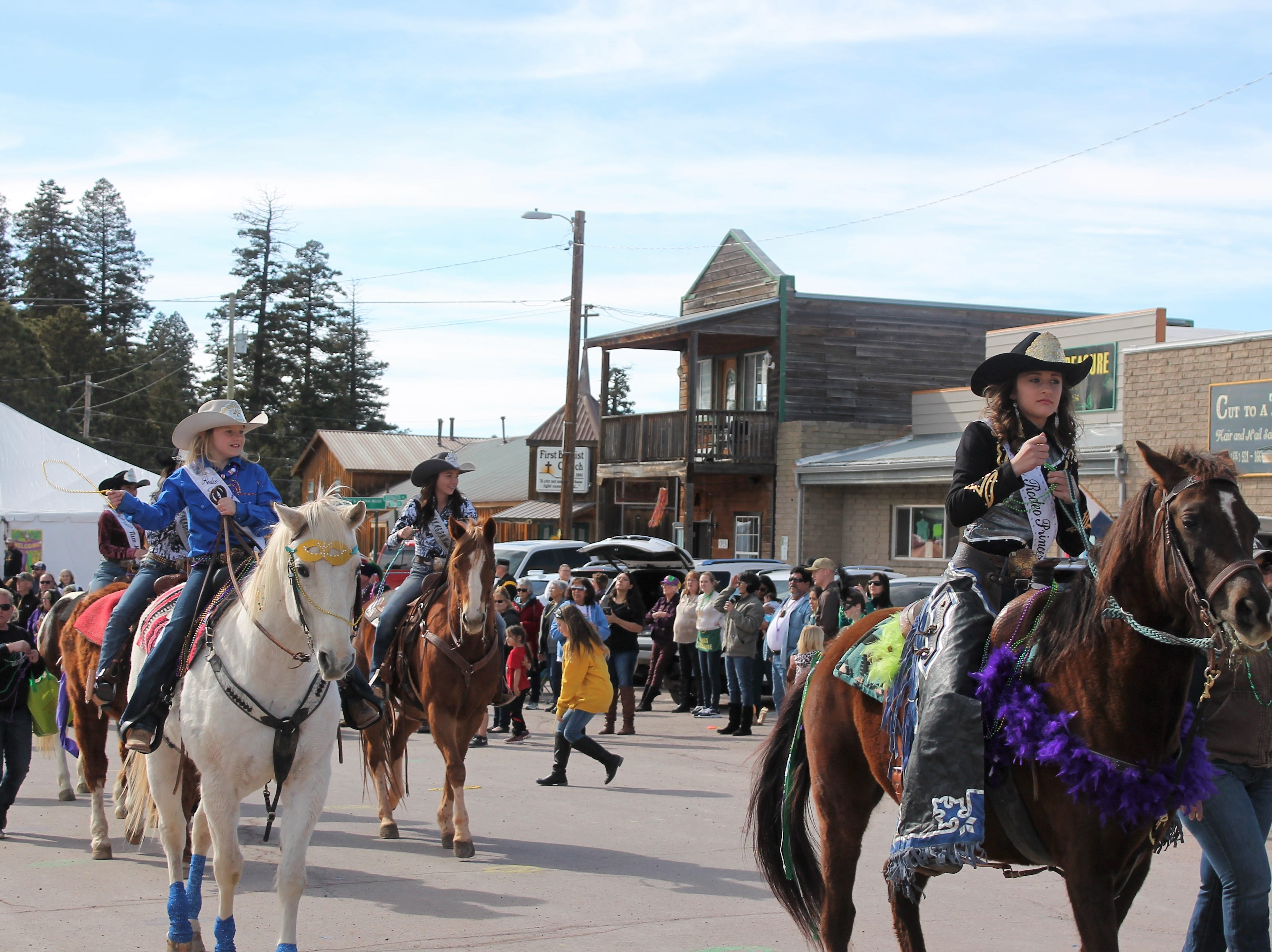 The Rodeo Queens throw beads at the Mardi Gras Parade in Cloudcroft Saturday.