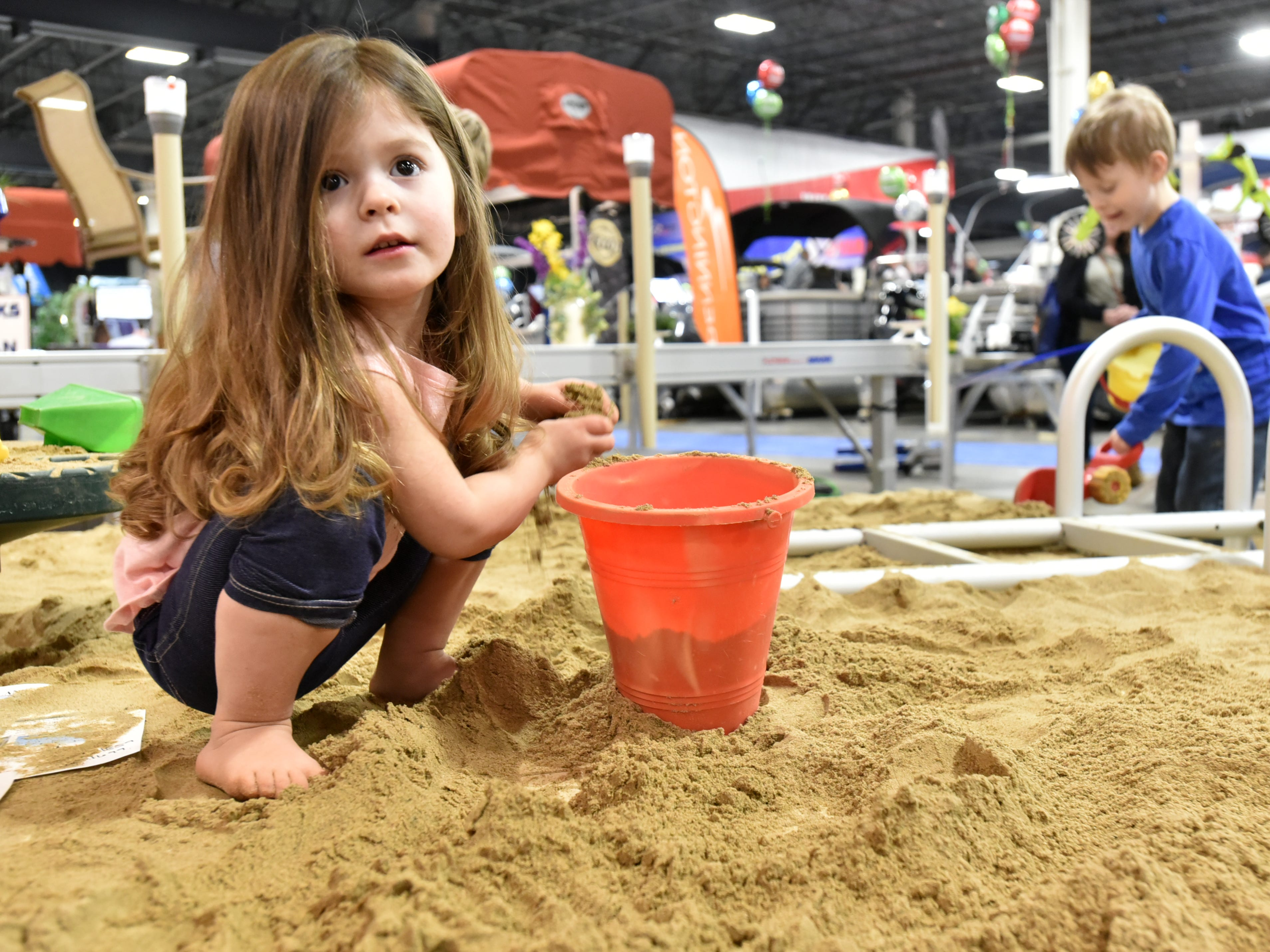 Avery Thom, of St. Clair Shores, plays in a giant sand box at the recently-concluded Outdoorama at Novi's Suburban Collection Showplace. The Outdoorama was combined with a show on cabin and up north living and had lots of exhibits on the outdoors and activities for the visitor to check out.