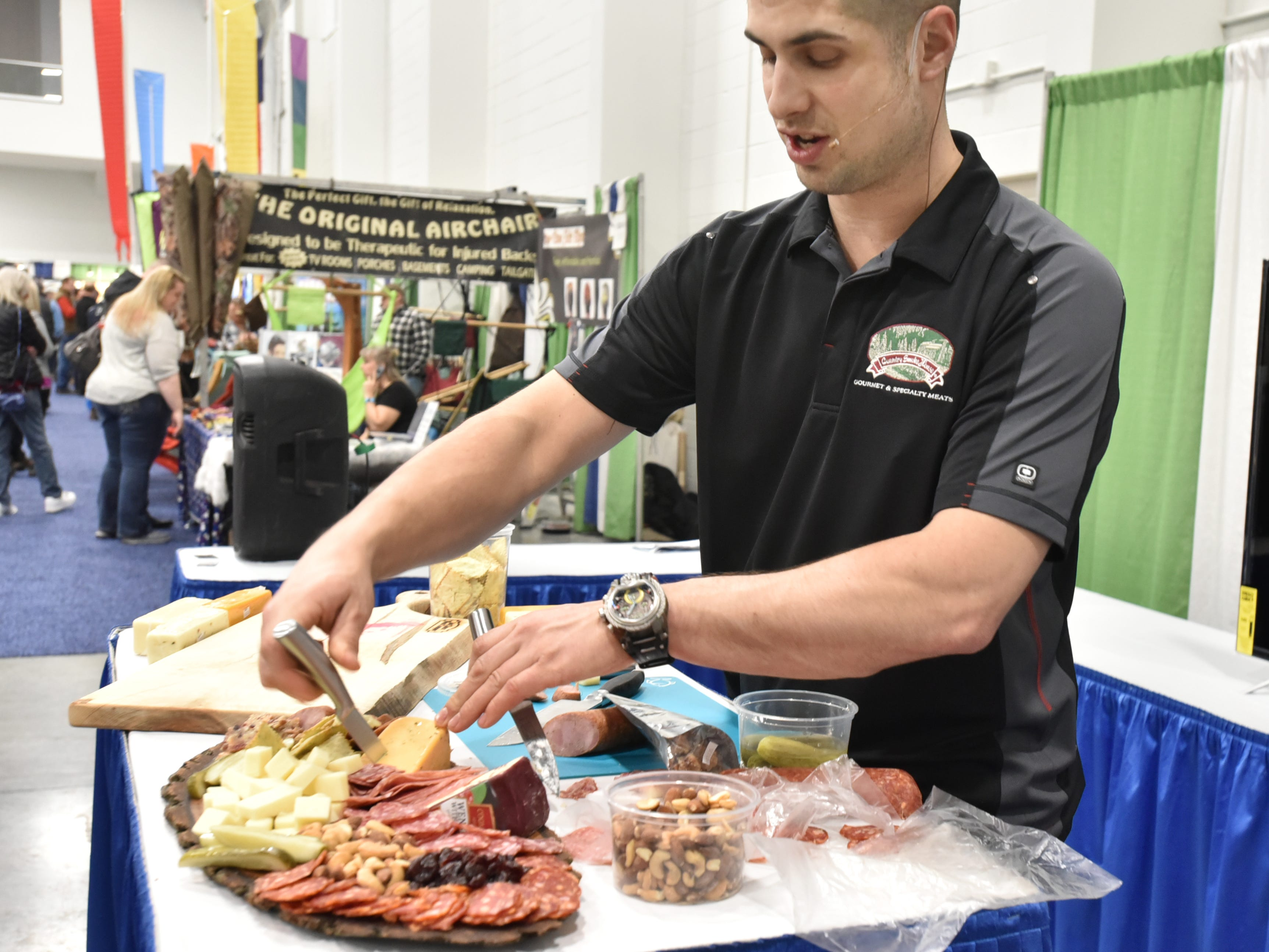 Stephen Francis, a representative of Country Smoke House meats shows a typical charcuterie plate on Saturday, March 2nd's Outdoorama in Novi.