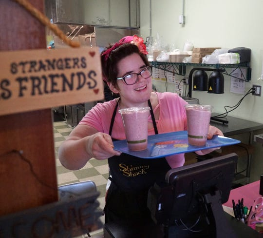Jessica Messing hands over a couple of vegan strawberry milkshakes to go on March 4.