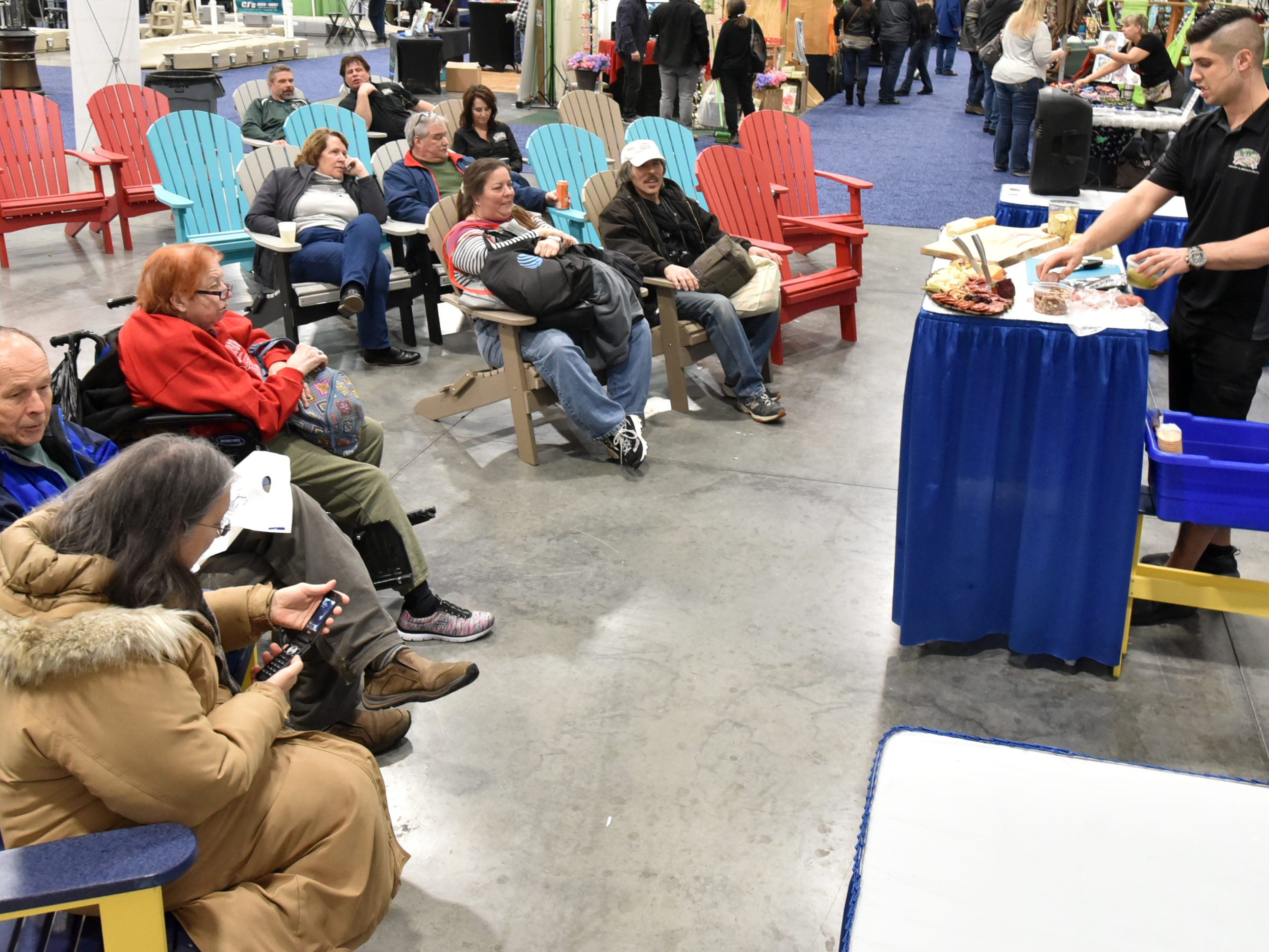 Visitors to the March 2nd Outdoorama at Novi's Outdoorama relax in some Adirondack-style chairs as they watch a culinary exhibit.