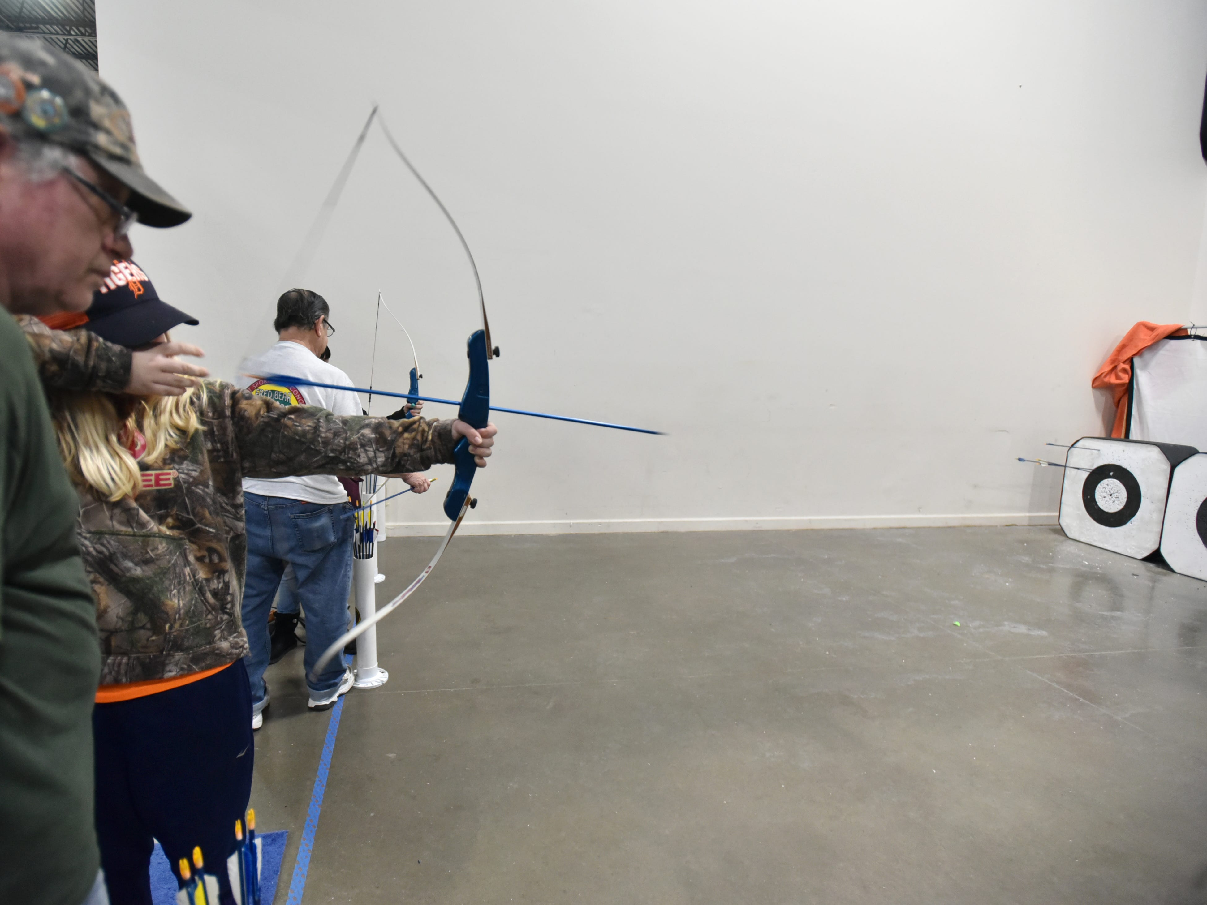 Alyssa Antio tries her hand at some archery at the Michigan Bow Hunters exhibit at the Outdoorama.