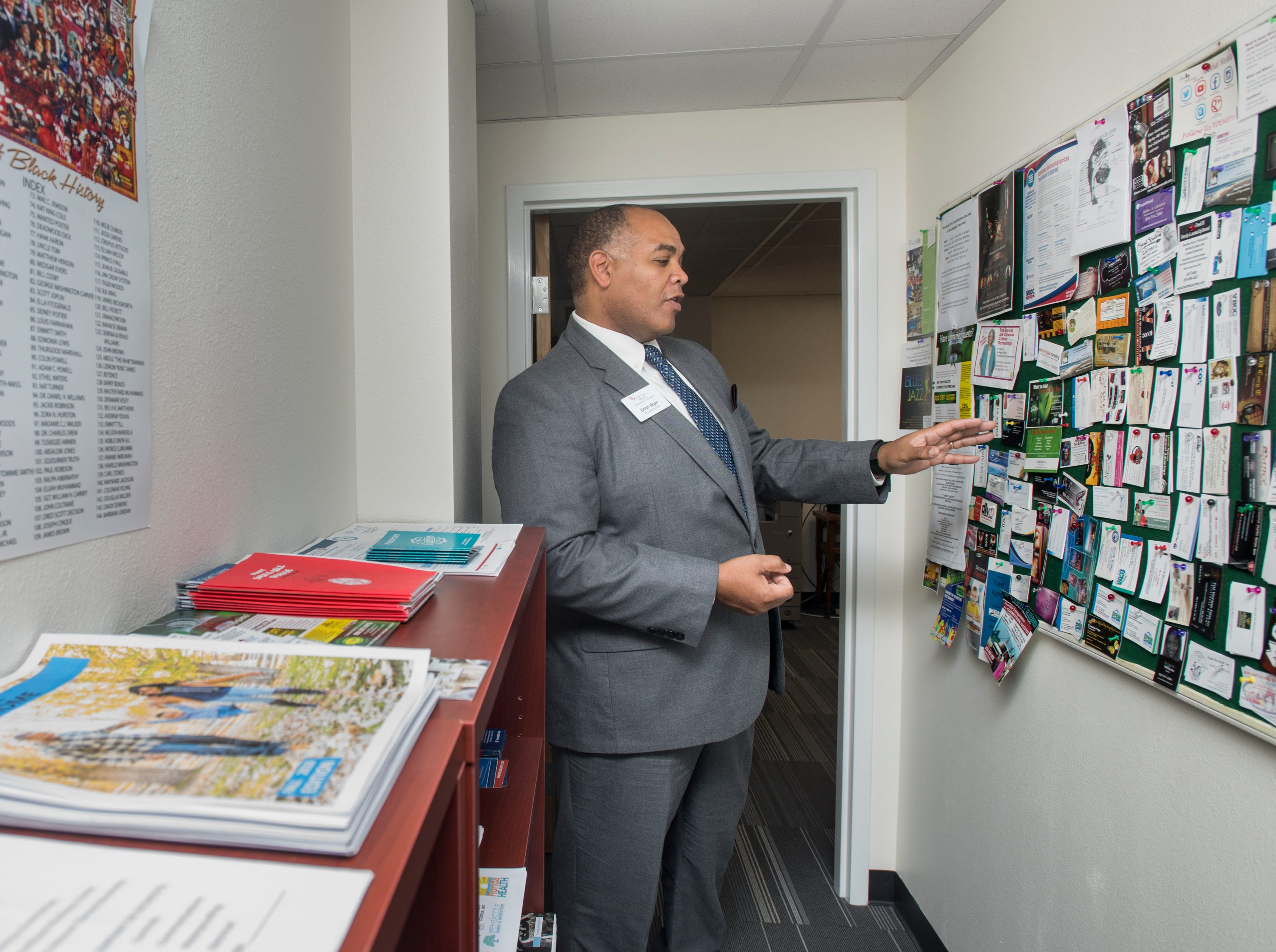Brian Wyer, President/CEO of the Gulf Coast Minority Chamber of Commerce, points out business cards from African-American owned businesses hung at his office in downtown Pensacola on Monday, March 4, 2019.