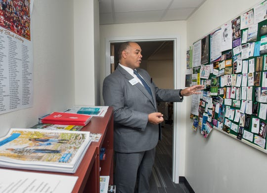 Brian Wyer, president and CEO of the Gulf Coast Minority Chamber of Commerce, points out business cards from African-American owned businesses at his office in downtown Pensacola on March 4.