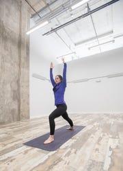 Heather Hill practices yoga poses Disko Lemonade in downtown Pensacola on Monday.