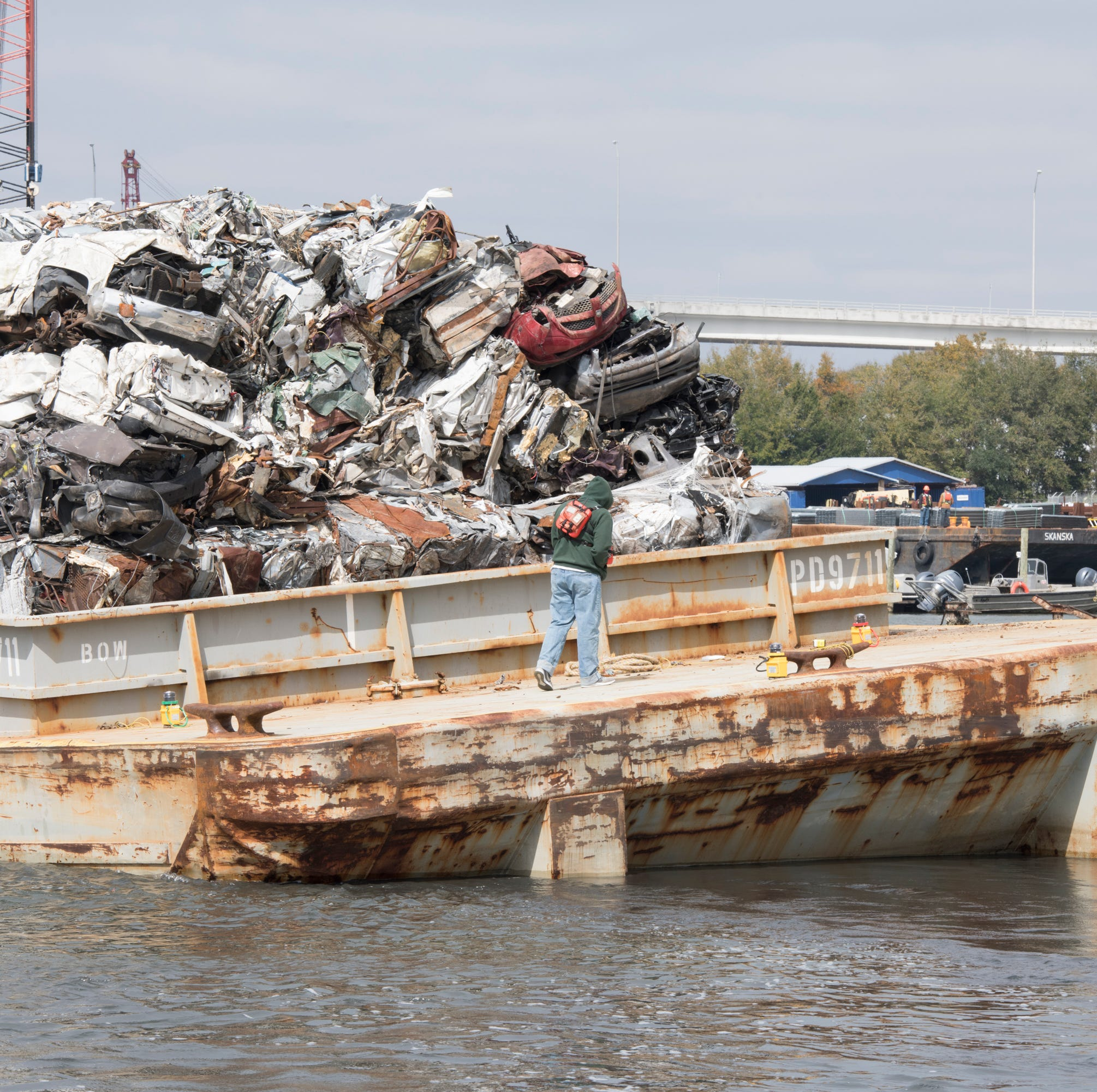 Barges carrying crushed cars run aground in Bayou Chico, separate from tug boat