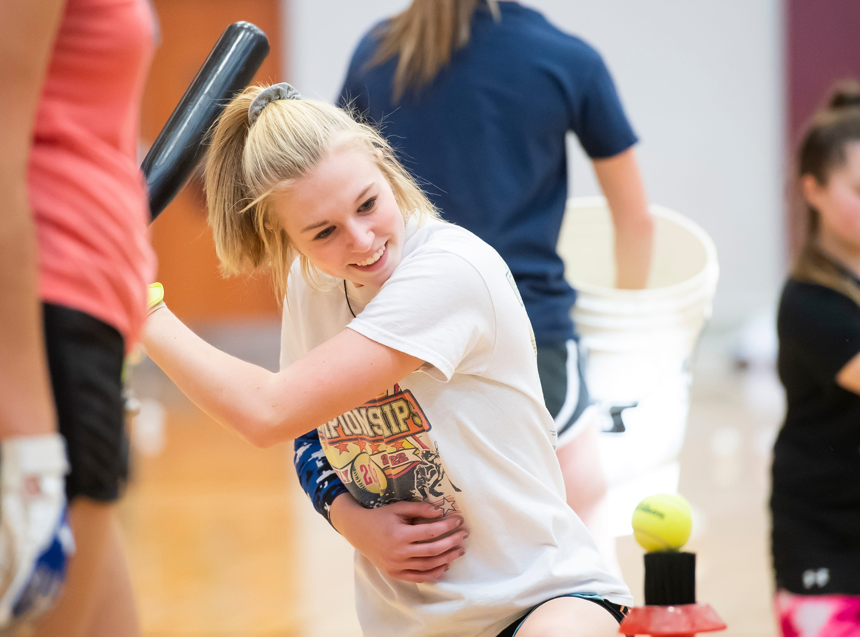 Gettysburg's Abby Hurst prepares to swing during a kneeling backhand tee drill on the first day of softball practice inside the Gettysburg High School gym Monday, March 4, 2019.