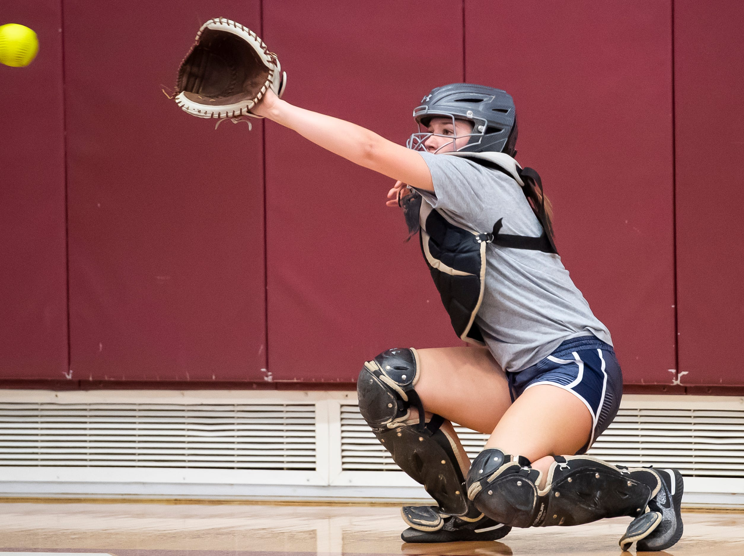 Gettysburg's Kaelyn Blocher reaches to catch a ball from a pitcher during the first day of softball practice inside the Gettysburg High School gym Monday, March 4, 2019.
