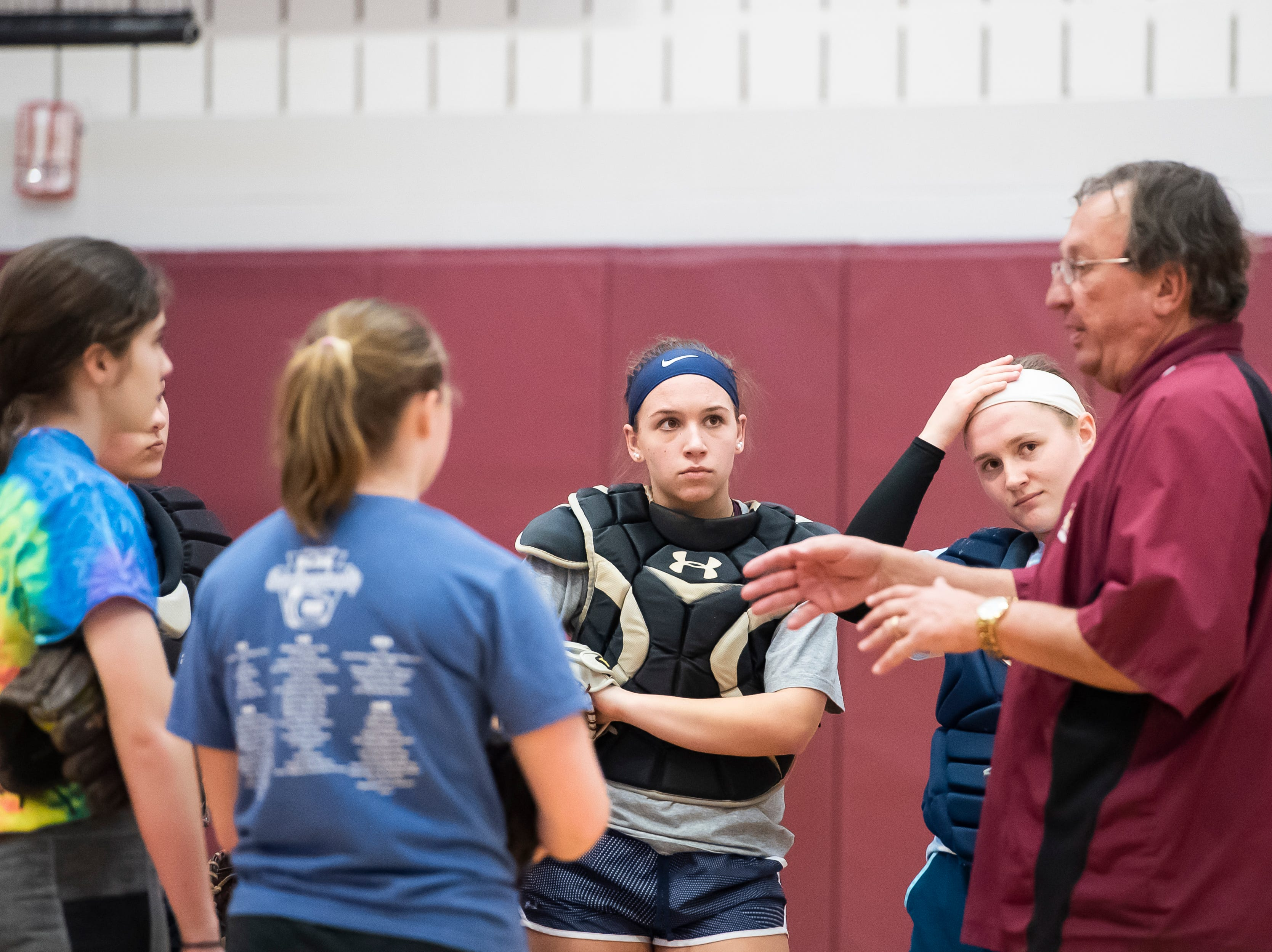 A group of Gettysburg softball catchers and pitchers listen to assistant coach Bernie Yannettie on the first day of softball practice inside the Gettysburg High School gym Monday, March 4, 2019.