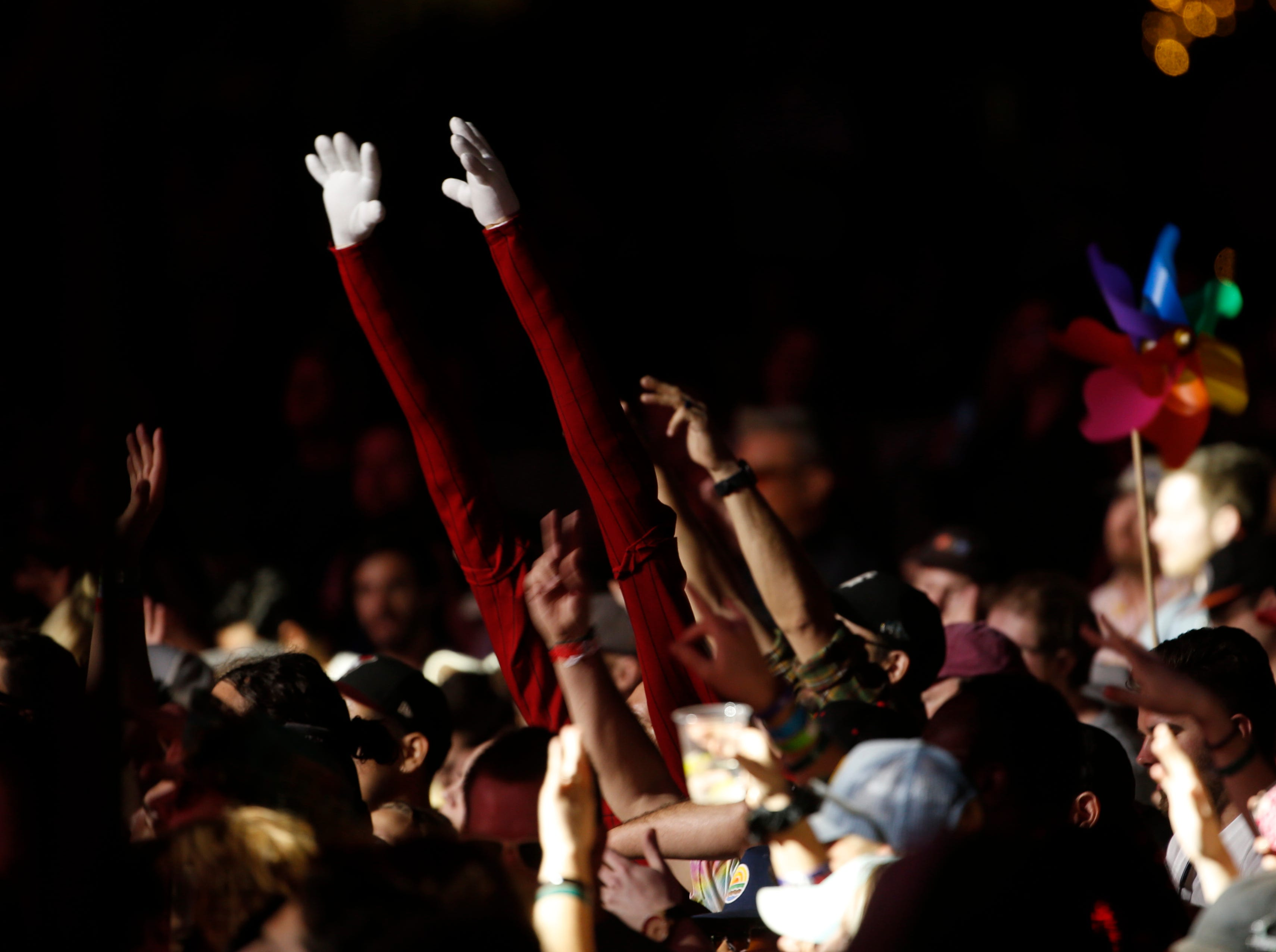 A fan with fake long arms listens to Lettuce perform during McDowell Mountain Music Festival in Phoenix on March 3, 2019.