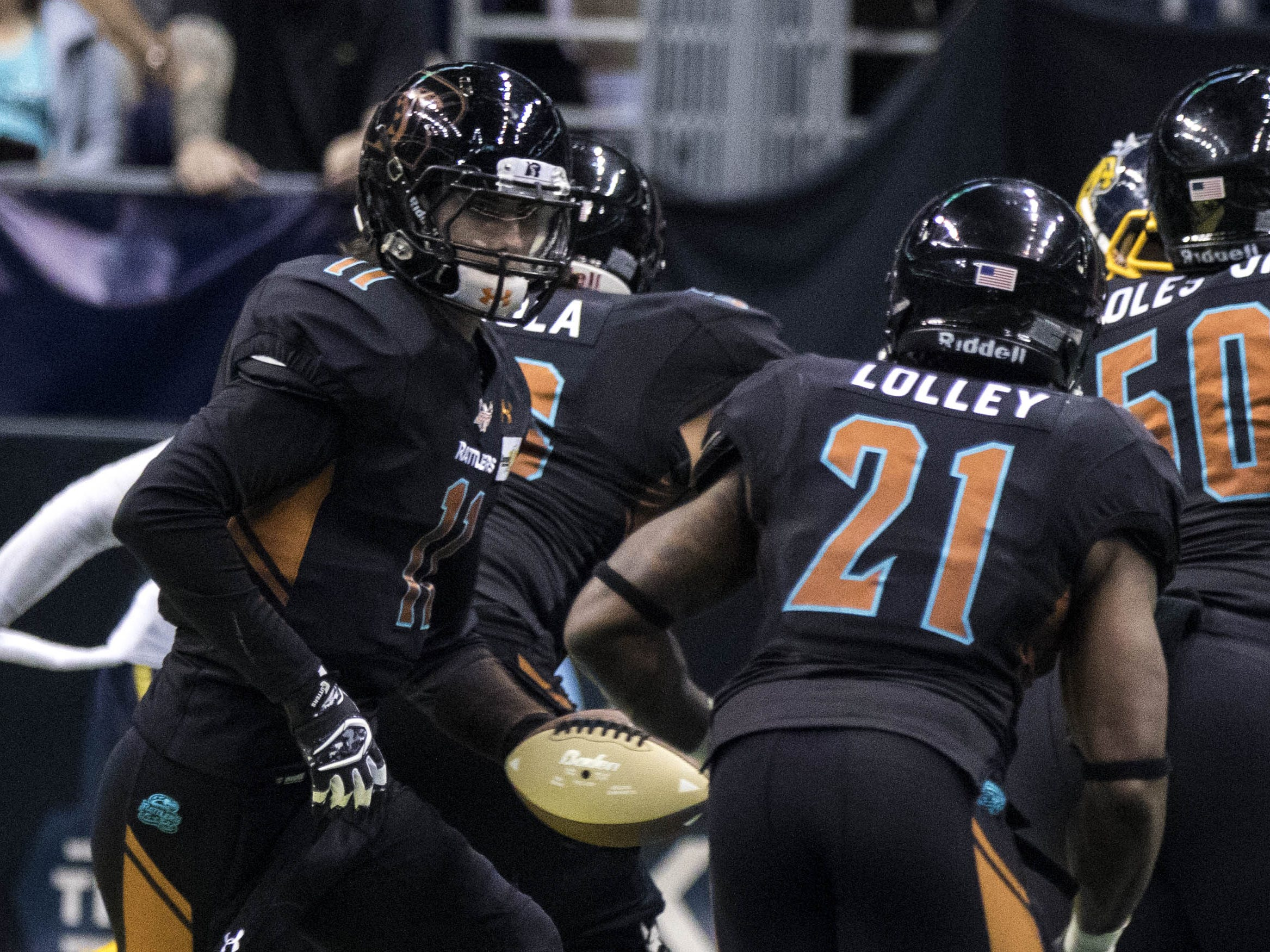 Arizona Rattlers' Jeff Ziemba (11) hands the ball off to  Jabre Lolley (21)  during the second half of their game at Talking Stick Resort Arena in Phoenix, Sunday, March 3, 2019.