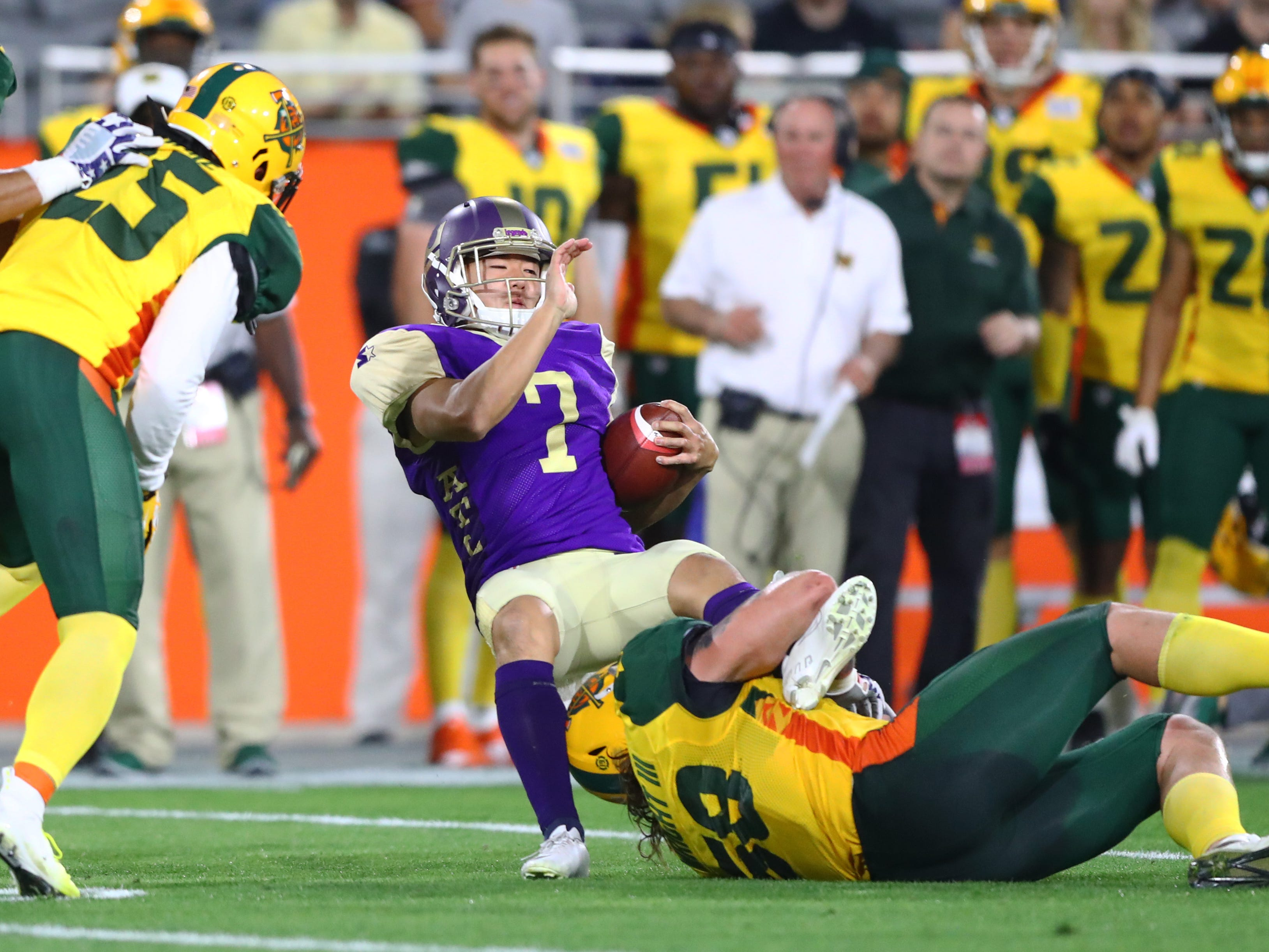 Mar 3, 2019; Tempe, AZ, USA; Atlanta Legends kicker Younghoe Koo (7) is tackled by Arizona Hotshots linebacker Scooby Wright III during the first half of an AAF football game at Sun Devil Stadium.