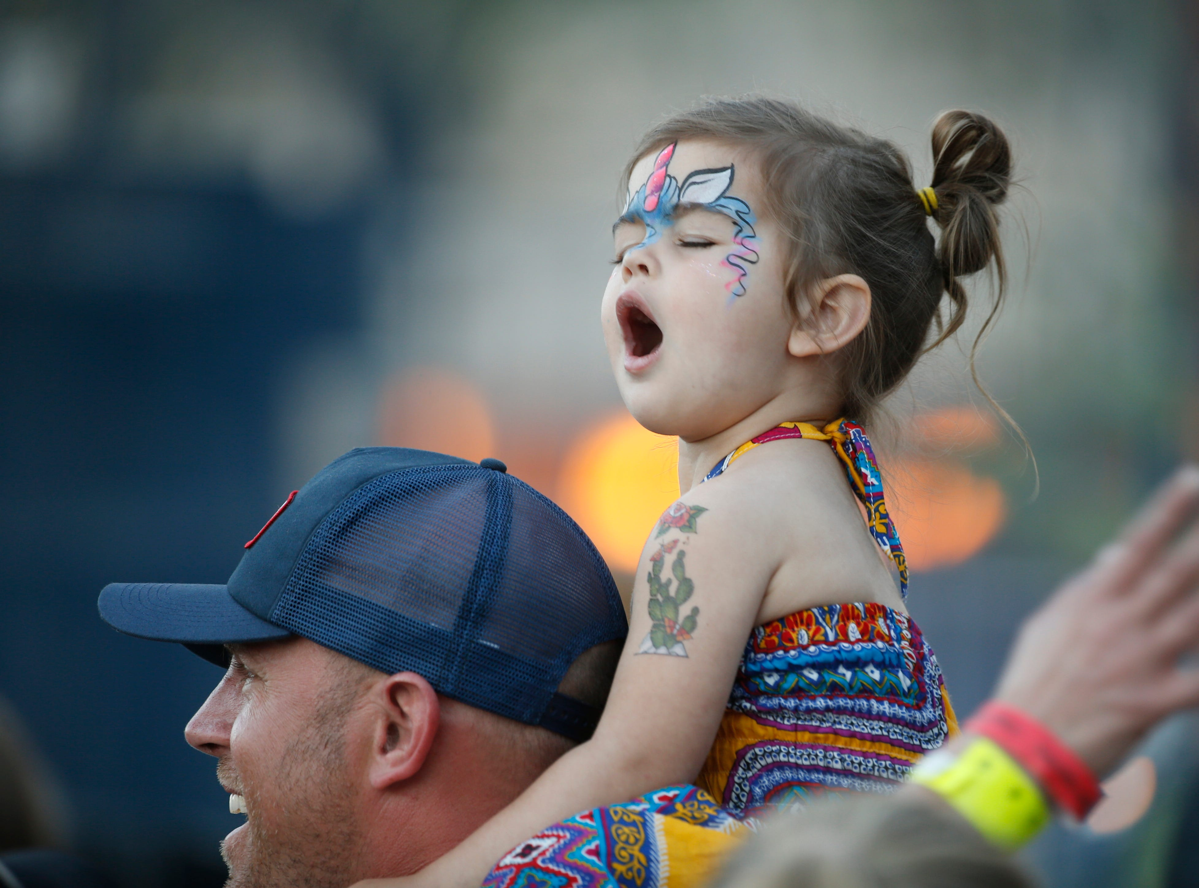 Marcus DeGraff carries his daughter Addie DeGraff as she sings during House of Treezus' performance during McDowell Mountain Music Festival in Phoenix on March 3, 2019.