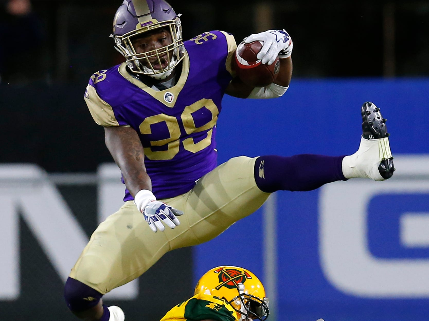 Atlanta Legends running back Brandon Radcliff (39) leaps over Arizona Hotshots defensive back Robert Nelson (21) in the first half during an AAF football game, Sunday, March 3, 2019, at Sun Devil Stadium in Phoenix.