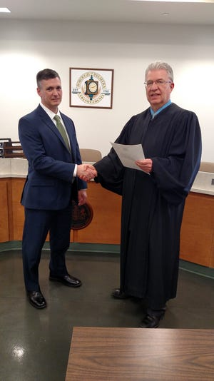 Andrew Winters, the new Palmyra police chief (left), is sworn into office Monday, March 4 by magisterial district judge Carl Garver.