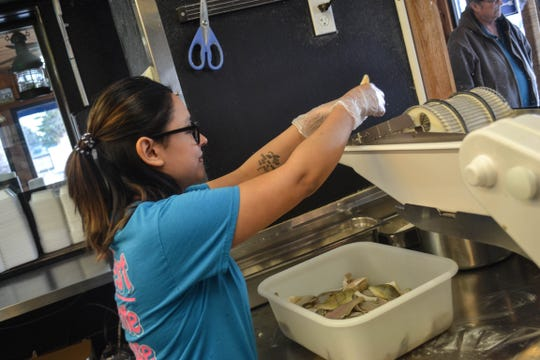 Cook Raeanne Alvarez loads Lake Erie perch into the breading machine. Customers can watch staff clean and bread fish through a window that separates the dining room from the kitchen.