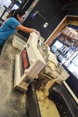 Cook Raeanne Alvarez loads Lake Erie perch on one end of the breading machine while breaded fish drop from the other end.
