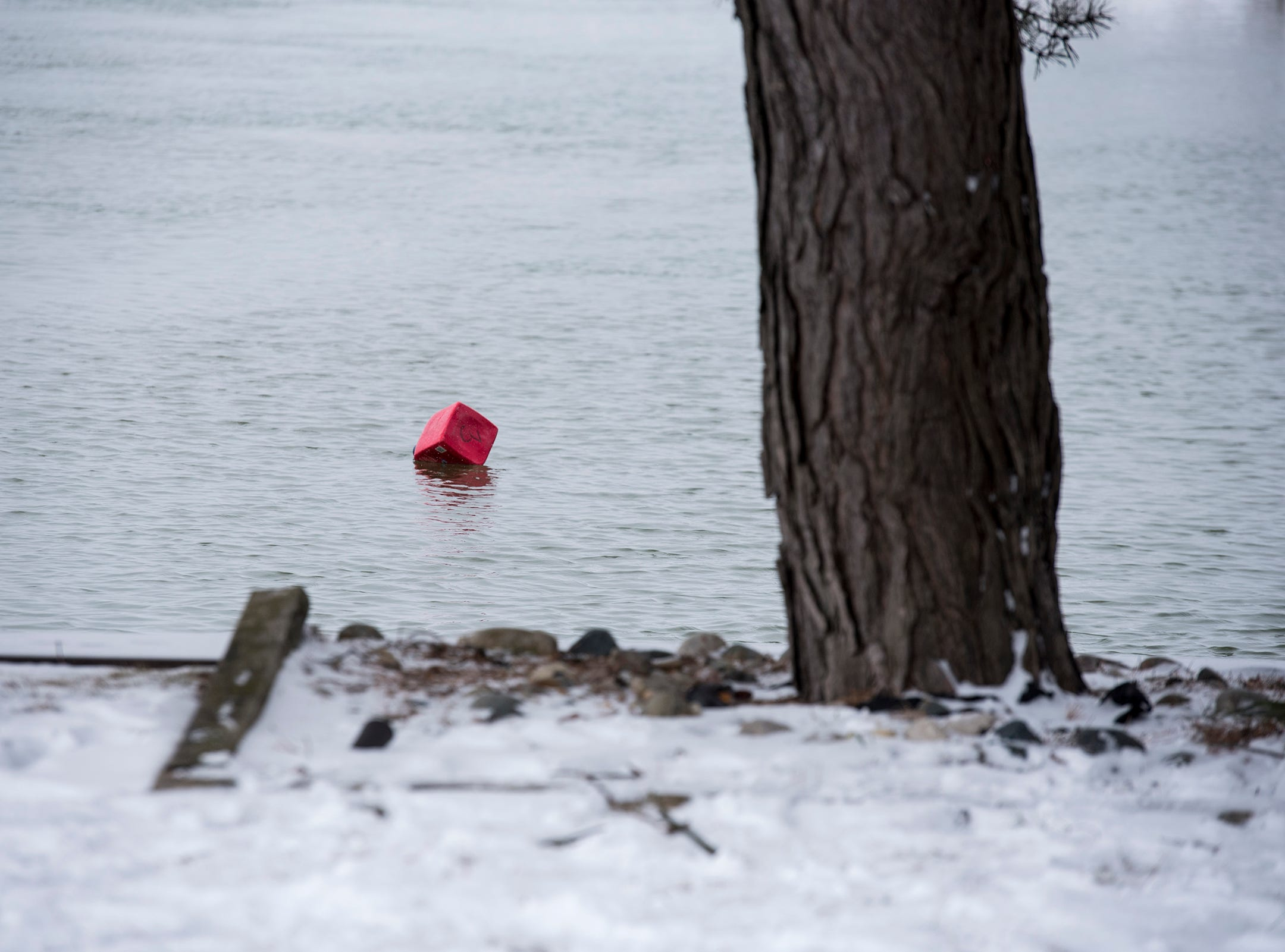 A red buoy marks the location of a vehicle that went into the water Monday, March 4, 2019, where the Belle River and St. Clair River meet in Marine City. Police spotted tracks appearing to enter the waterway in the 1300 block of South Water Street shortly before 9:30 a.m. A body was discovered in the water.