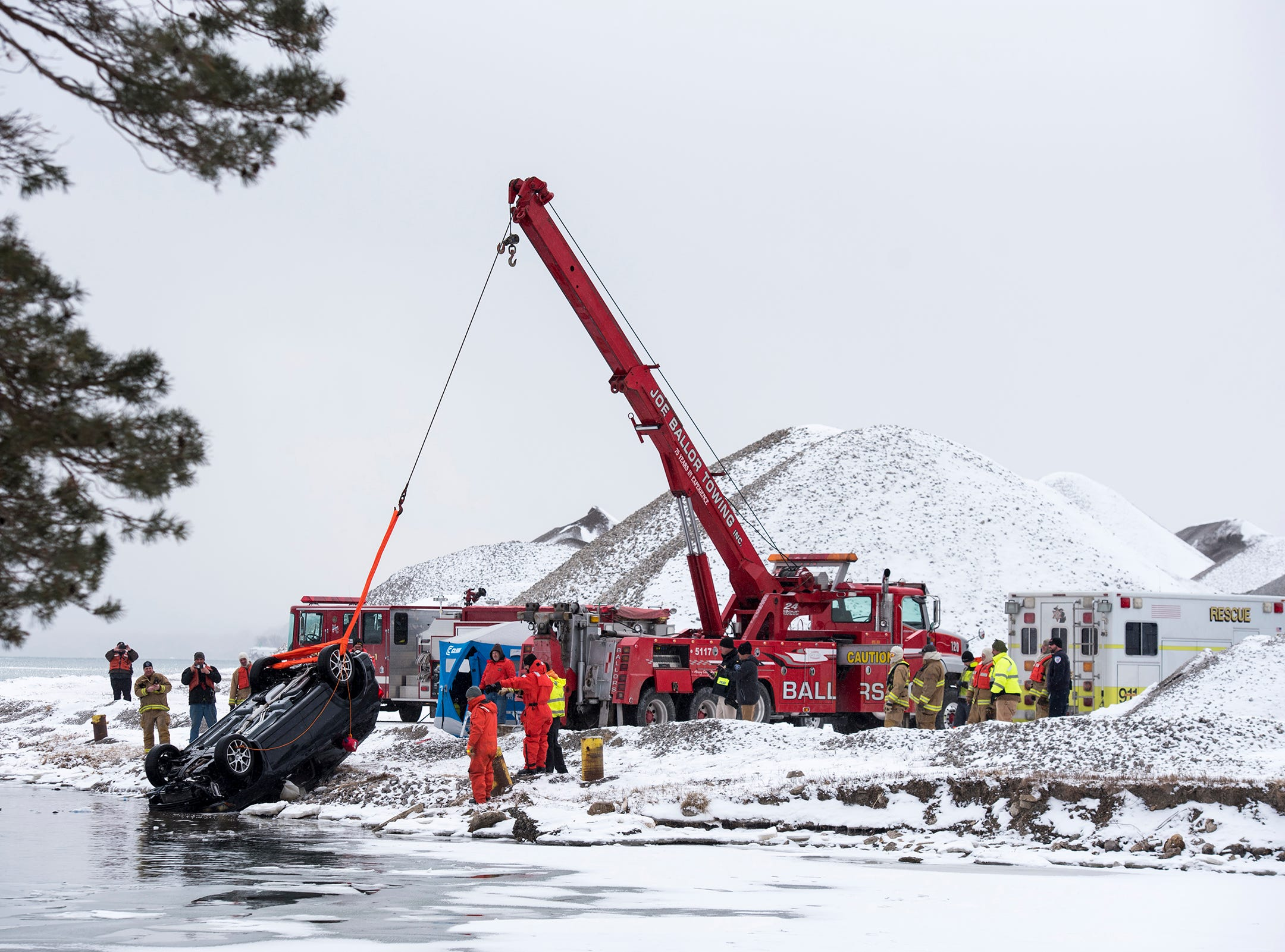 Crews remove a vehicle from the water near where the Belle River meets the St. Clair River Monday, March 4, 2019 in Marine City.
