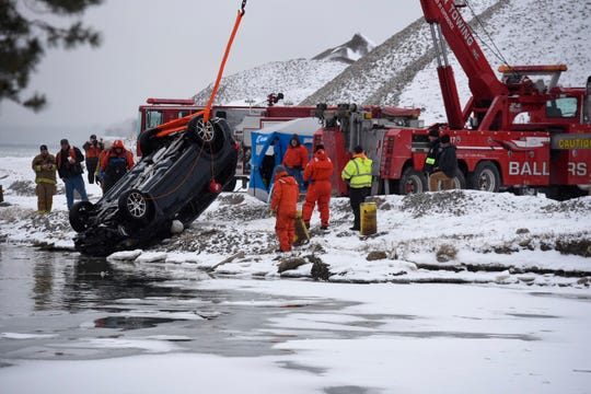 Crews remove a vehicle from the water near where the Belle River meets the St. Clair River in Marine City Monday morning.