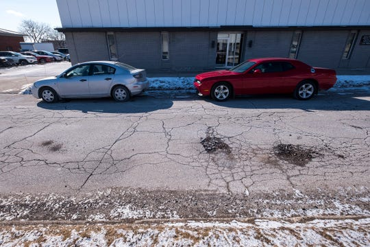 Cars are parked on the shoulder of McMorran Boulevard near several large potholes Monday, March 4, 2019 in Port Huron.