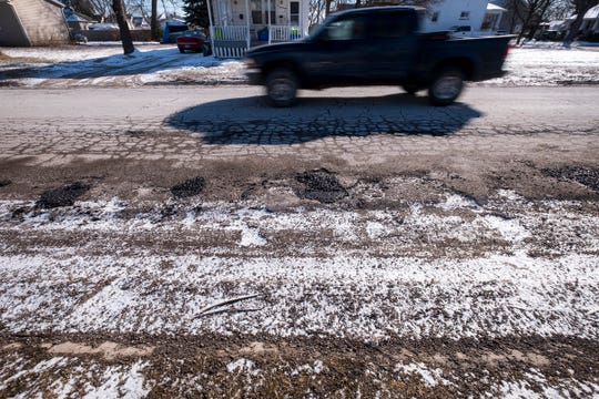 A vehicle drives past potholes and cracks in the pavement on 13th Street Monday, March 4, 2019 in Port Huron.