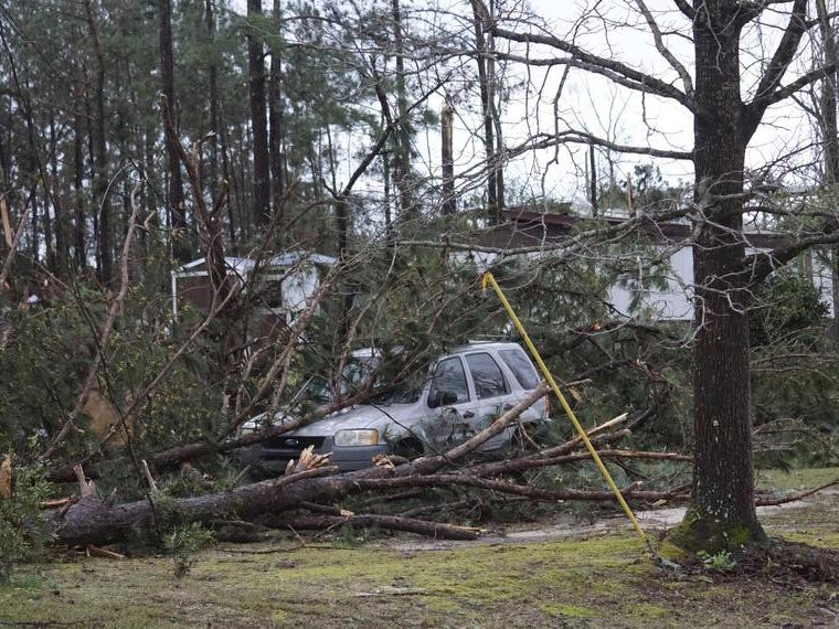 A vehicle is caught under downed trees along Lee Road 11 in Beauregard, Ala., Sunday, March 3, 2019, after a powerful storm system passed through the area. (Kara Coleman Fields/Opelika-Auburn News via AP)