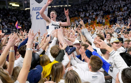 Fans celebrate with Utah State forward Justin Bean on the court after Utah State defeated Nevada 81-76 on Saturday.