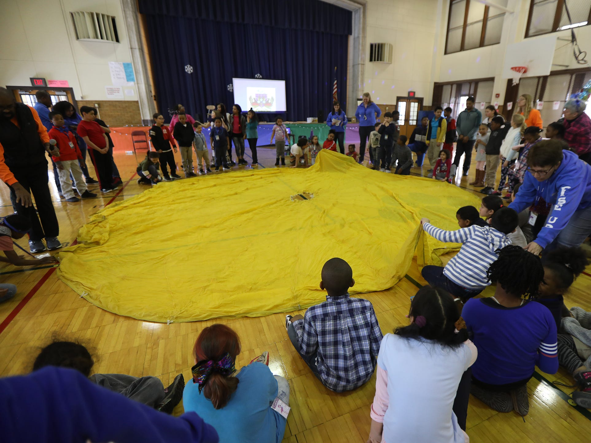A group that rotated into the gym, sit, getting ready for the next round of a parachute game during House Day where the school invites parents in while they celebrate and continue teaching principles of each house.  The students and teachers are divided into four houses at RISE Community School.