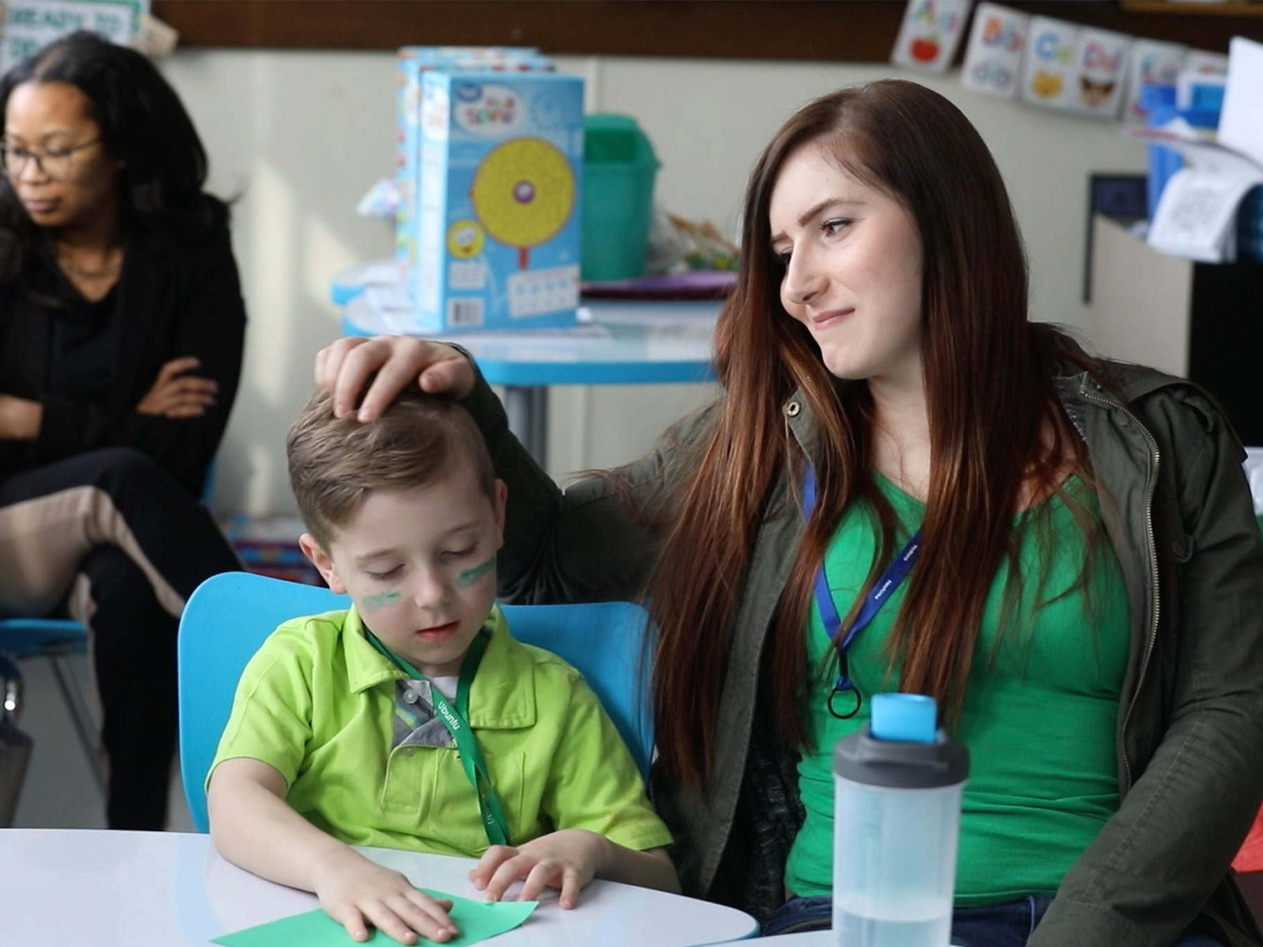 Jessica Calkins caresses her son, Matthew, a kindergartner, before the students start working on an activity.  Parents were invited to attend RISE House Day which takes place during the last couple hours of the school day,