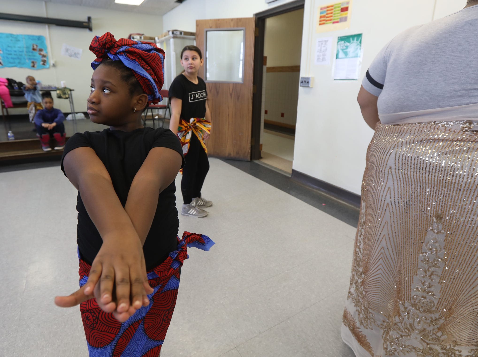 Dorie Lewis looks up at one of the adults who was reminding her about the opening moves during dance practice for Black History Month celebration at RISE Community School.  Several girls came in during February break to practice for the end of the month performance.
