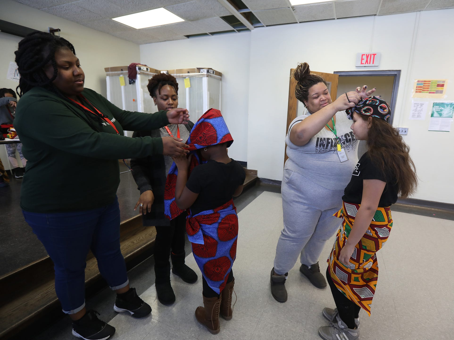 Jolanta Davis helps Shaquana Reed tie the wrap around Dorie Lewis's head while Tyshauna Clark puts Madison Ramos's on during their dance practice at Rise Community School.  Davis and Reed are with AmeriCorps, one of the school's community partners, and are at the school five days a week.  Clark is the community school coordinator for RISE Community School.