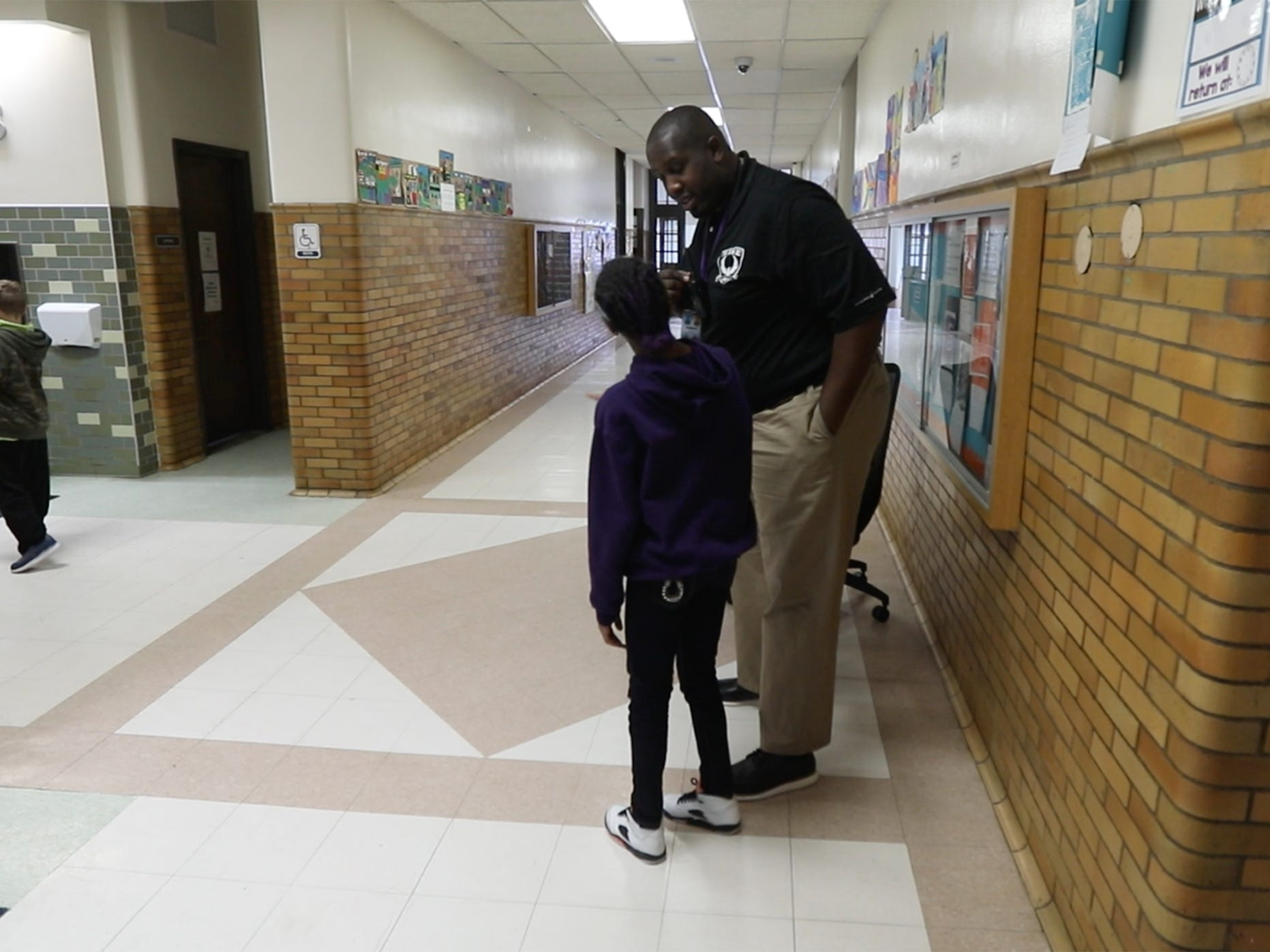 James Reaves, assistant principal at RISE Community School, greets a student as students passed to attend their house event.