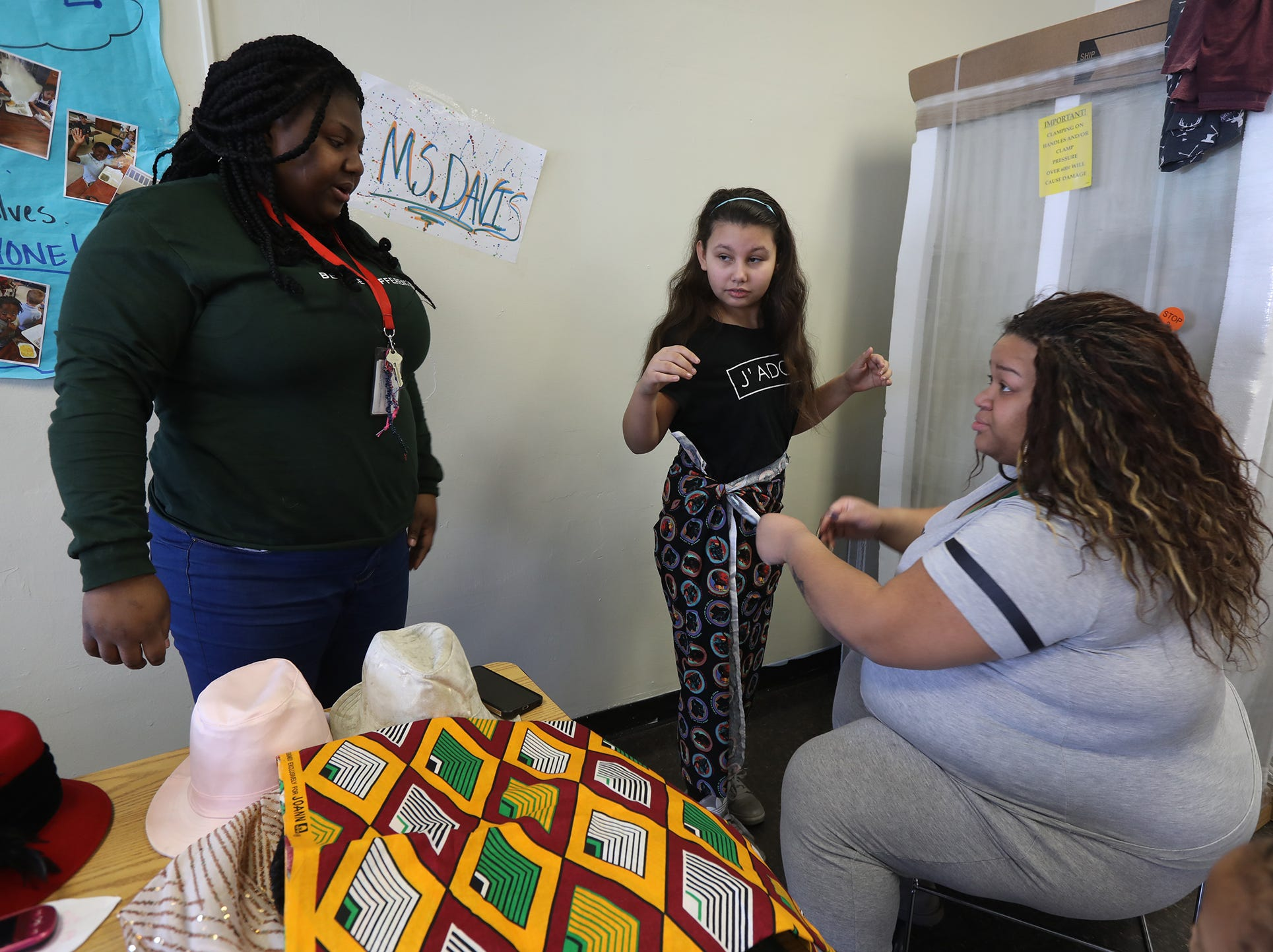 Jolanta Davis with AmeriCorps talks with Tyshauna Clark, the community school coordinator at RISE Community School talk about the costumes while Clark fits Madison Ramos with her costume.  Some of the students came in during February break to practice a performance for Black History Month they will put on at the school.