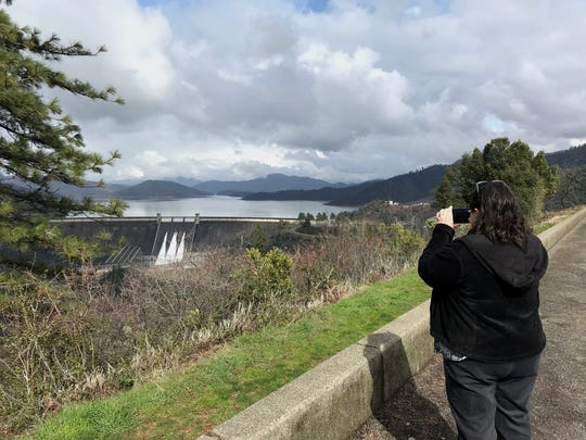 Denise Miraldi of Fairfield takes a photo of Shasta Dam on Tuesday, which was releasing 30,000 cubic-feet per second of water.