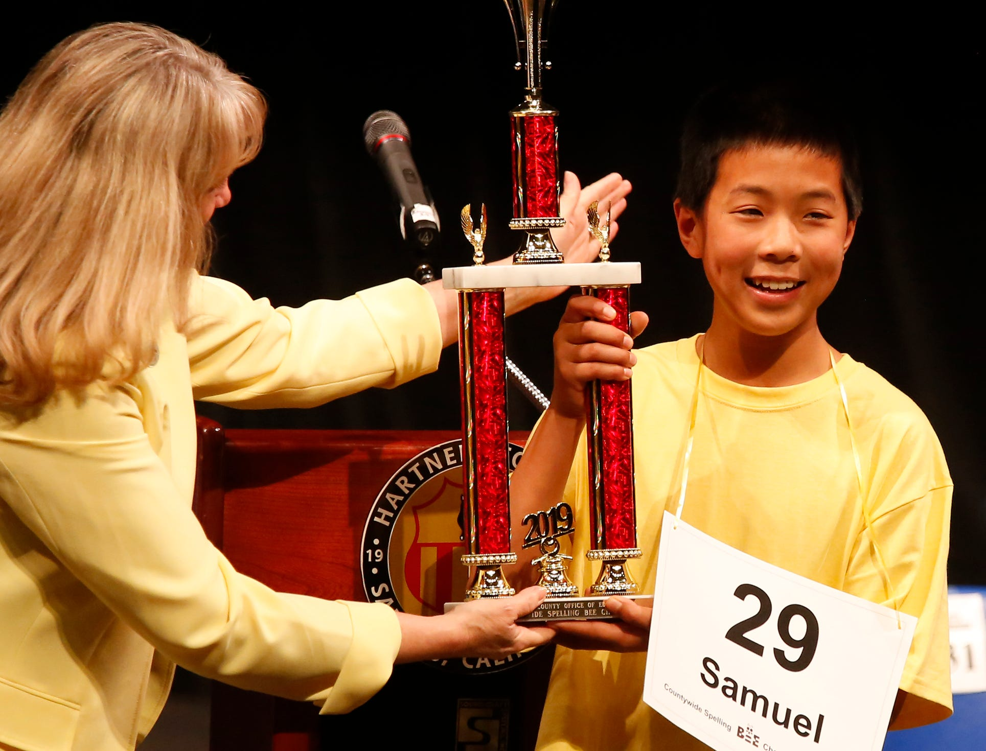 Monterey County Superintendent of Schools Deneen Guss hands Washington Middle School eighth-grader Samuel Low the Countywide Spelling Bee trophy at Hartnell College in Salinas.