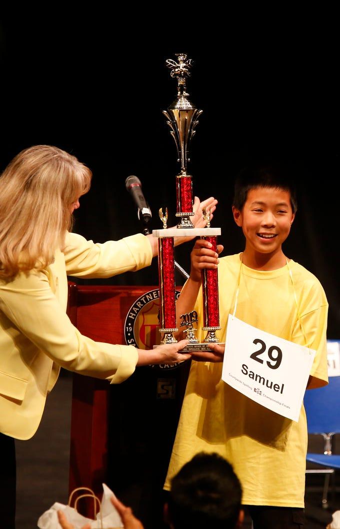 Monterey County Superintendent of Schools Deneen Guss hands Washington Middle School eighth-grader Samuel Low the Countywide Spelling Bee trophy at Hartnell College in Salinas.