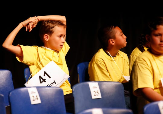 All Saints Episcopal Day School sixth grader Roy Reneker holds his arms over his head after successfully spelling a word during the Monterey County Office of Education's 2019 Countywide Spelling Bee.