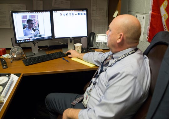 Charlottesville, Virginia, police Detective Declan Hickey looks at a photo of one of the men he is searching for in the beating of DeAndre Harris during the Unite the Right rally in 2017. Hickey is the lead detective on the case involving the beating in the Market Street parking garage.