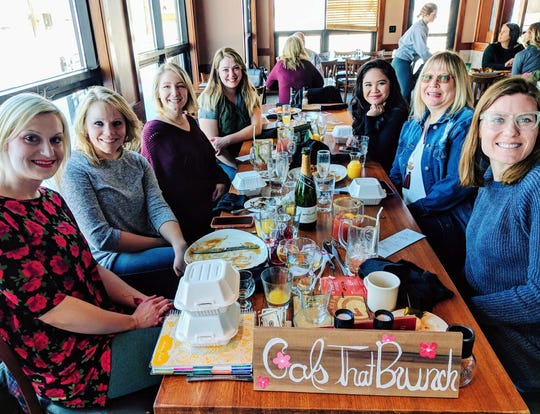 Andrea Tosse (front, left) founder of the St. Cloud chapter of Gals That Brunch, sits with launch attendees Sunday.