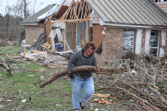 Kathy Byler moves a tree limb in her yard in a neighborhood of Baum Road where a tornado touched down Sunday March 3.