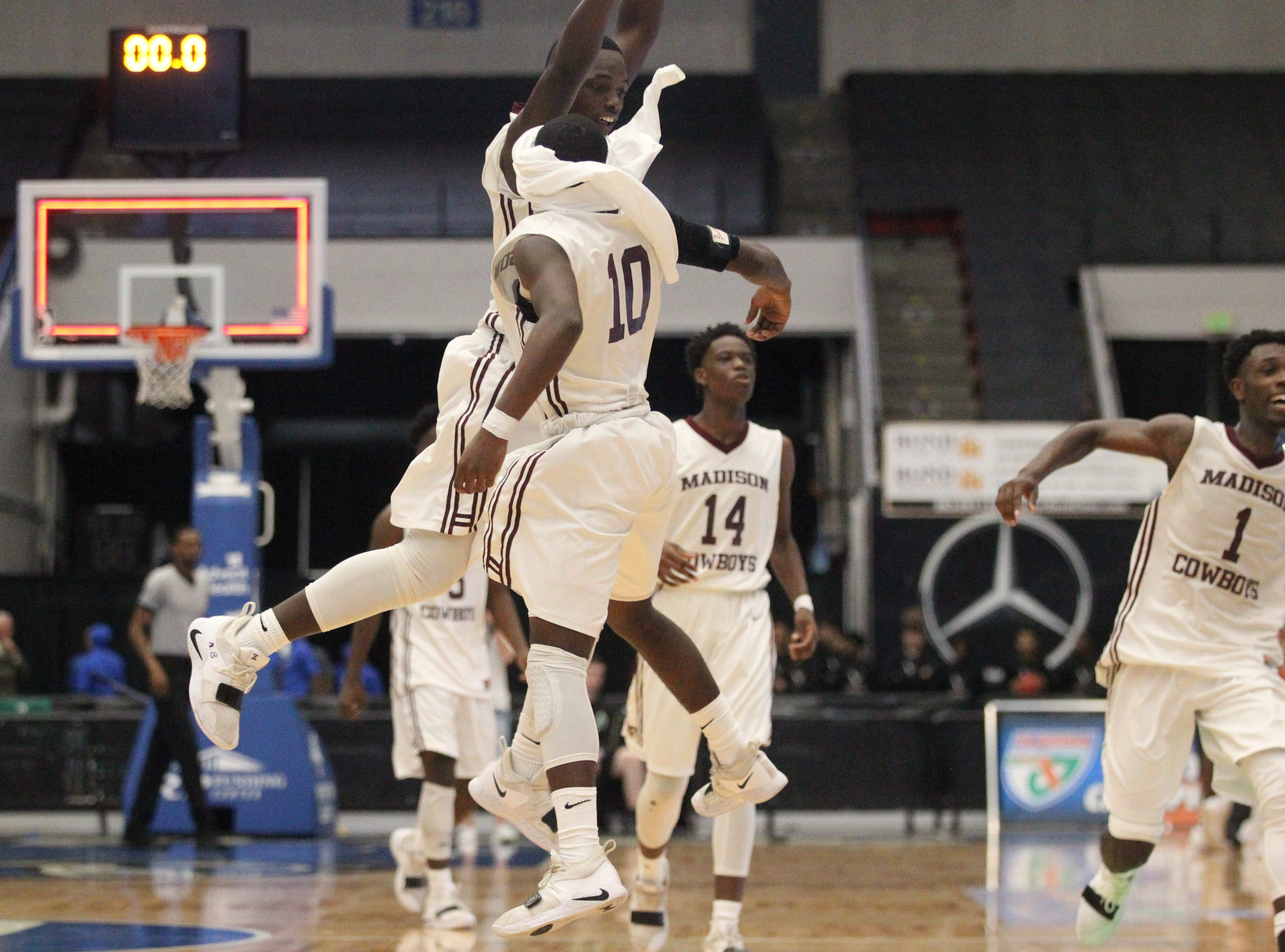 Madison County's Demarvion Brown  and Kelivon Oliver (10) chest bump after the Cowboys beat Paxton 63-51 during a Class 1A state semifinal game at the RP Funding Center in Lakeland on March 4, 2019.
