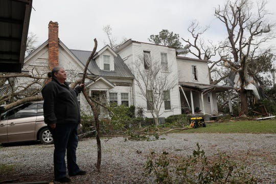 Tammy Esther, daughter of Ellen White, stands outside her mother's home and surveys the damage caused by a tornado that hit Cairo, Ga. Sunday night March 3, 2019.