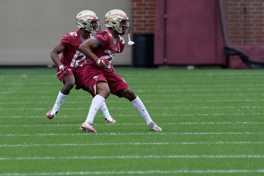 Defensive backs A.J. Lytton (12) and Asanta Samual Jr. (26) run drills during Florida State University football's first spring practice Monday, March 4, 2019.