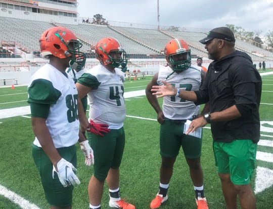FAMU associate head coach/tight ends coach James Spady (right) goes over plays with Nick Dixon (88), Veryl White (41) and Taymel Christian (47) during the first day of spring camp on Sunday, March 3, 2019.