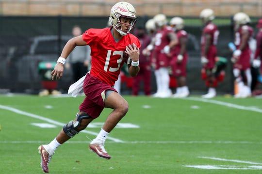 Quarterback Jordan Travis (13) runs the ball during Florida State University football's first spring practice Monday, March 4, 2019.
