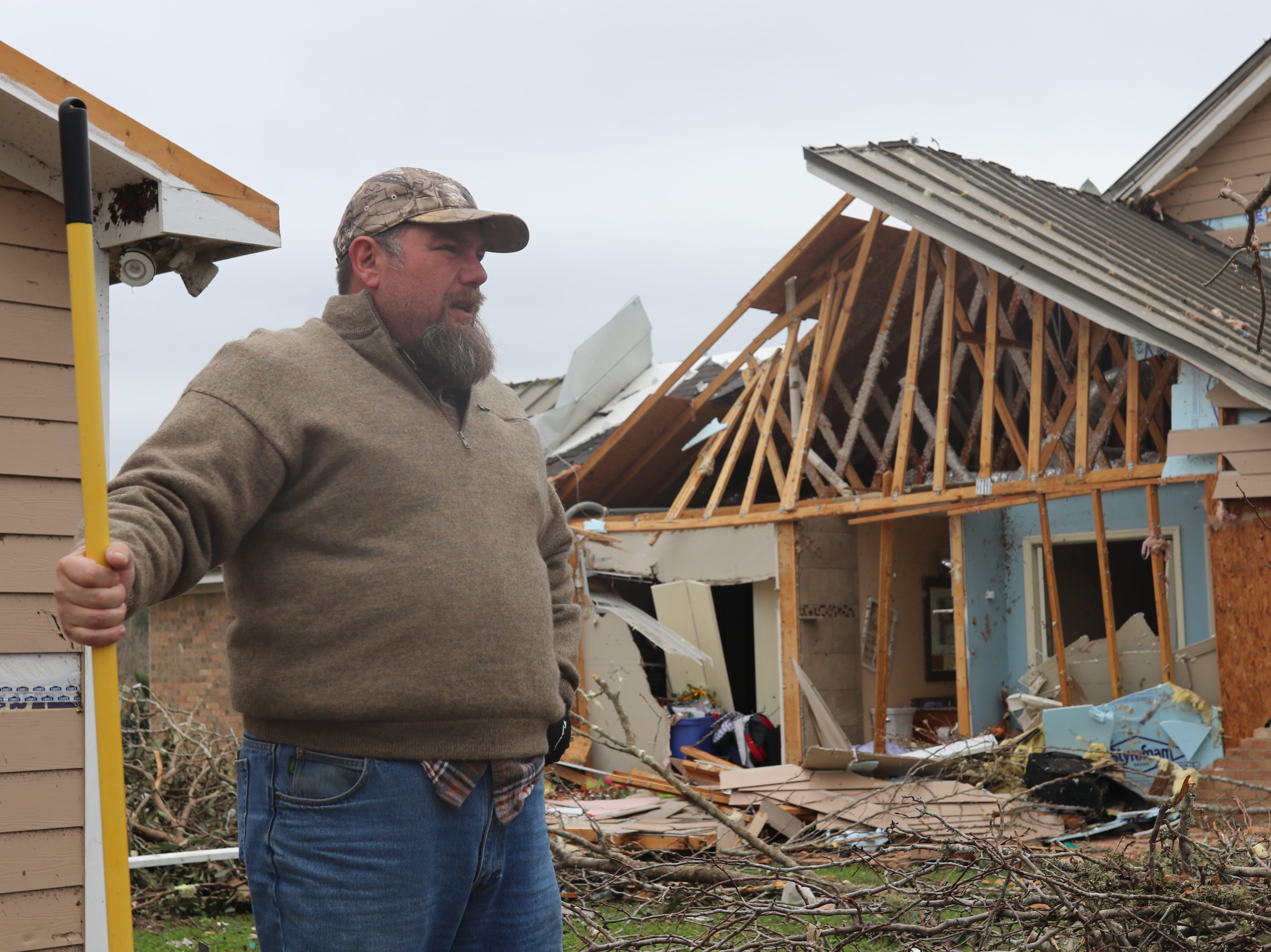 David Byler works to cleanup debris around his home which was severely damaged by a tornado Sunday March 3.