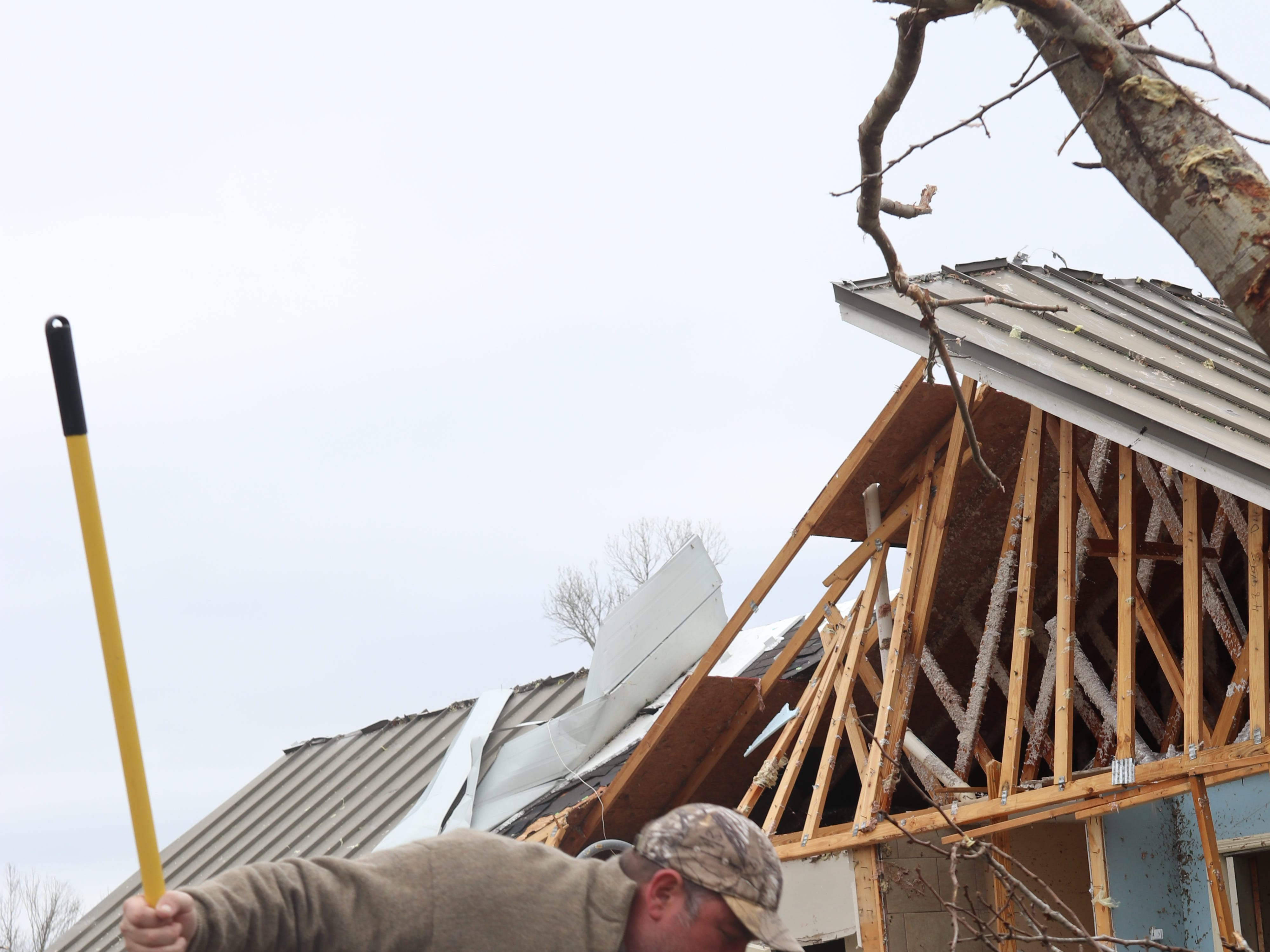 David Byler pulls photos from a pile of debris outside his home which was badly damaged by a tornado Sunday March 3.